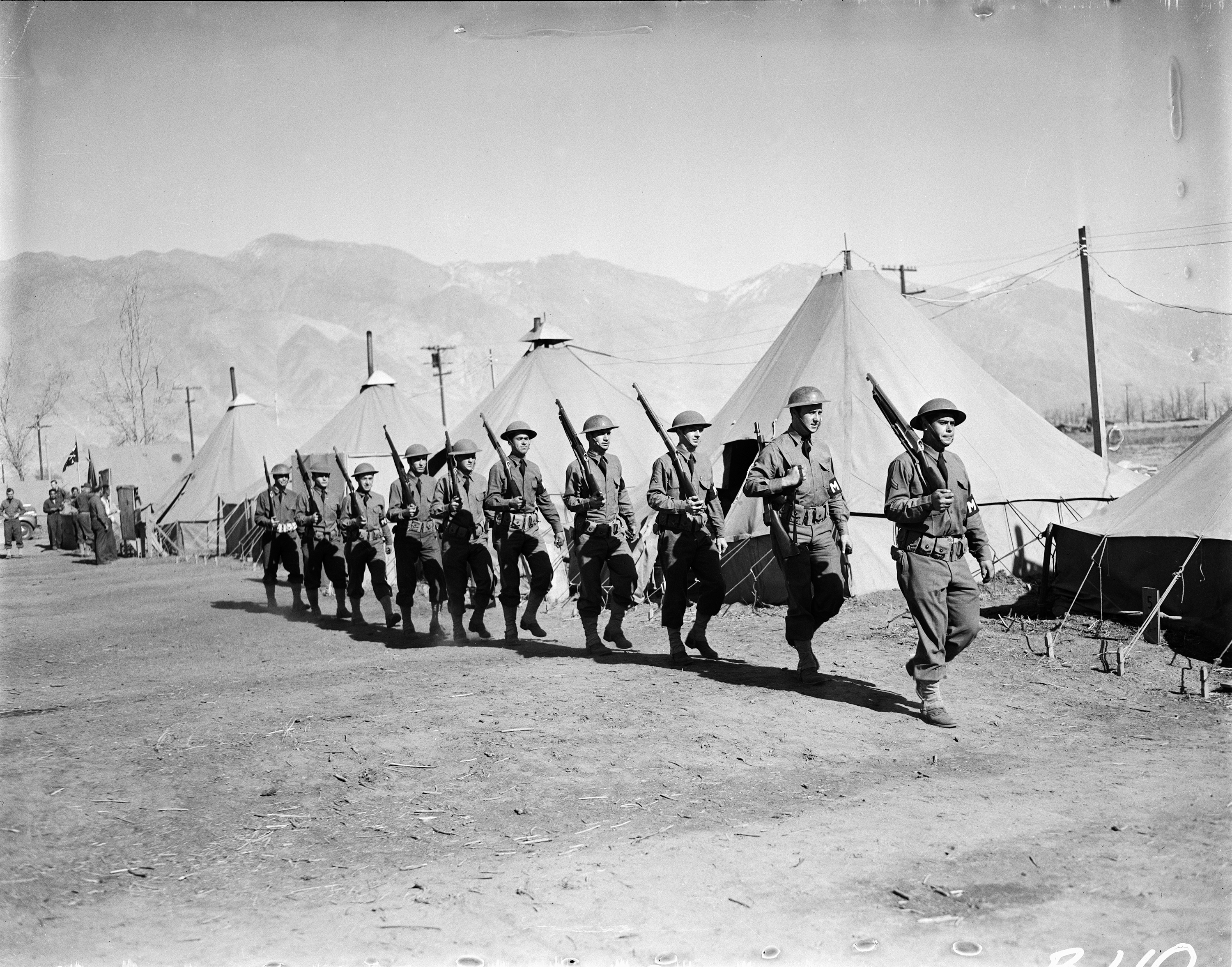 "A contingent of military police at the Manzanar Assembly Center. This ""assembly center"" was later converted into a permanent ""relocation center."""