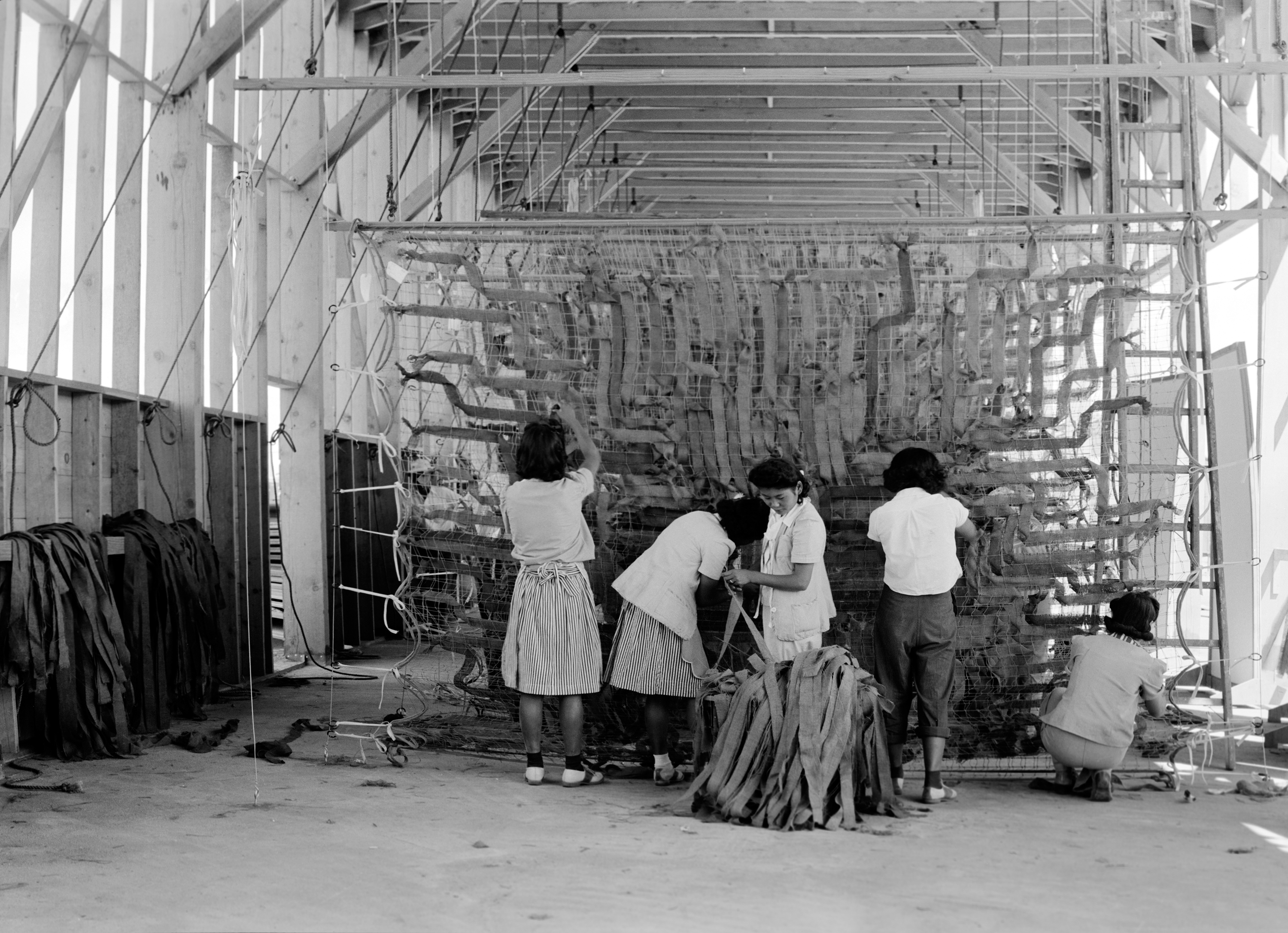 People incarcerated in the camps worked at a variety of jobs. These women at the Manzanar Relocation Center are making camouflage nets for the military. Dorothea Lange July 1, 1942