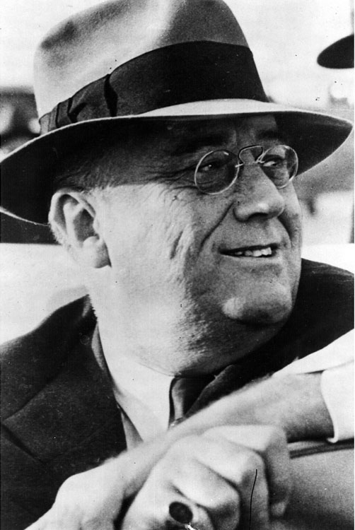 FDR wearing glasses and a hat, smiling, looking to the side